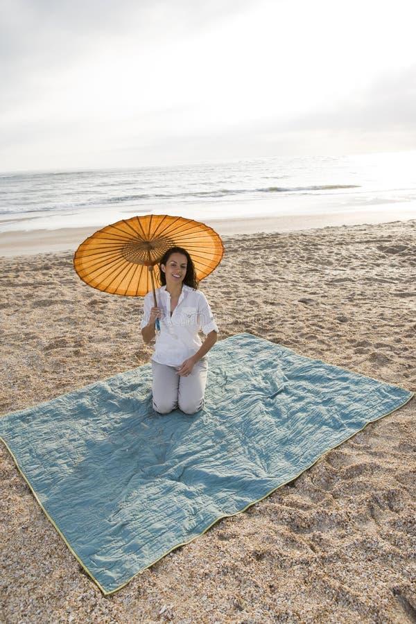 Free Hispanic Woman With Parasol On Beach Blanket Stock Photo - 14769740