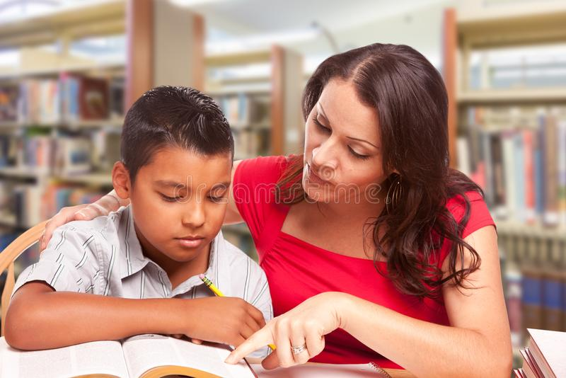 Hispanic Young Boy and Famle Adult Studying At Library stock images