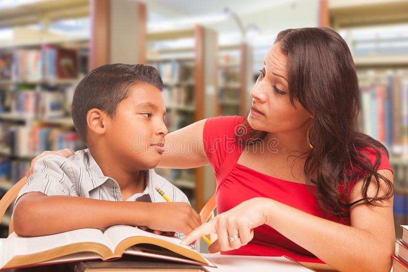 Hispanic Young Boy and Female Adult Studying At Library stock photography