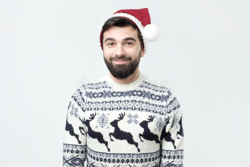 Hispanic young man with beard in a New Year cap. royalty free stock images
