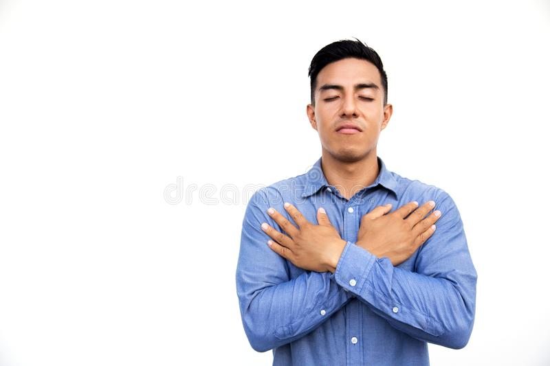 Hispanic young man in blue shirt is praying with closed eyes. stock images