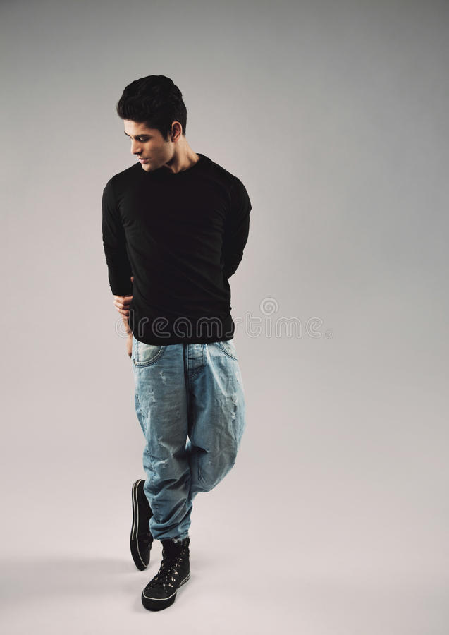 Hispanic young man in casuals posing on grey background stock images
