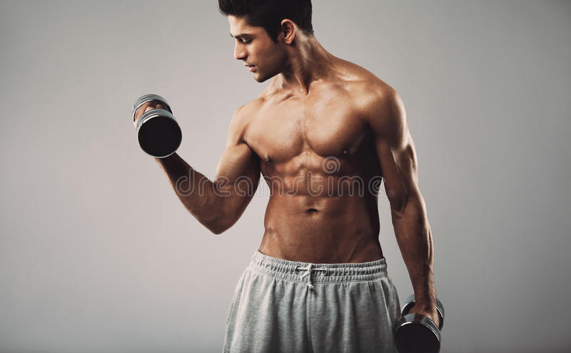 Hispanic young man doing heavy dumbbell exercise. Hispanic young muscular man doing heavy dumbbell exercise for biceps. Fitness male model working out with royalty free stock images