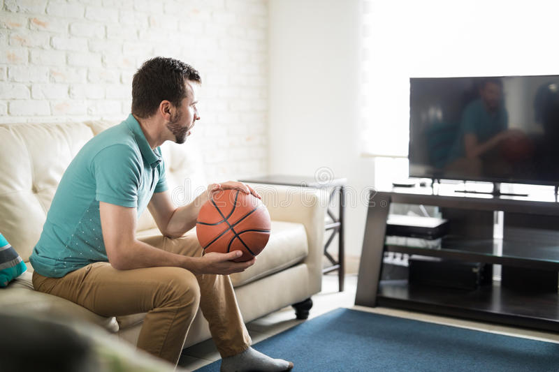 Attractive man watching basketball game. Hispanic young man relaxing at home watching a basketball game on tv and wearing casual clothes stock photography