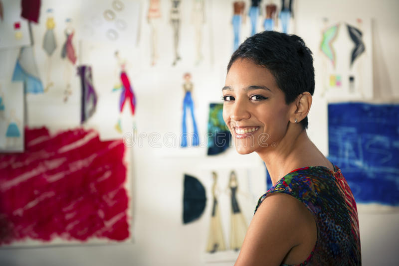 Hispanic young woman working as fashion designer royalty free stock photography
