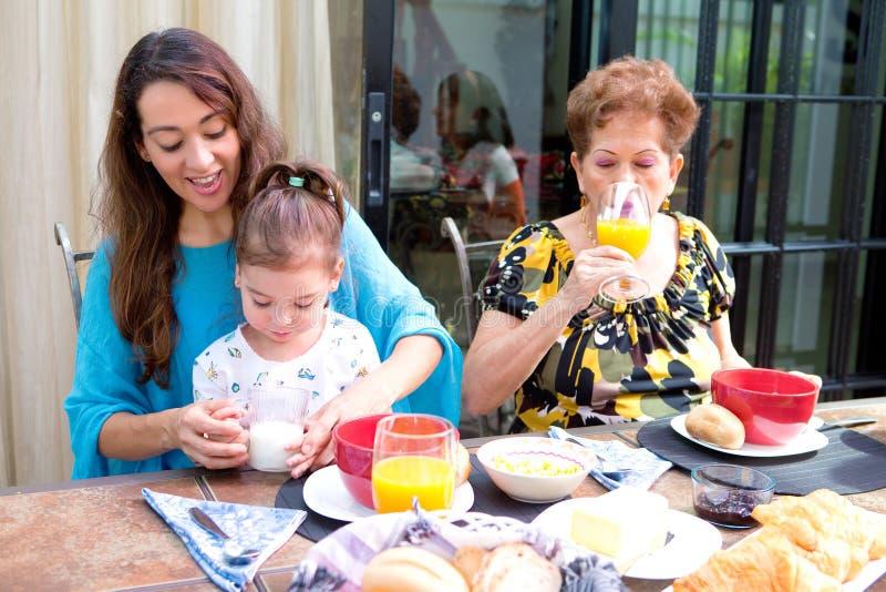 Hispanische Familie, die auf dem Speisen im Freien frühstückt lizenzfreie stockfotos