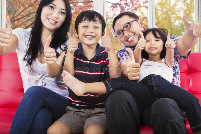 Hispanische Familie, die Daumen aufgibt stockbild