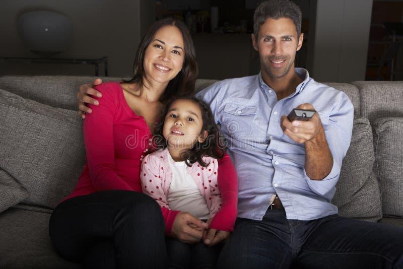 Hispanische Familie, die im Sofa And Watching Fernsehen sitzt lizenzfreie stockbilder