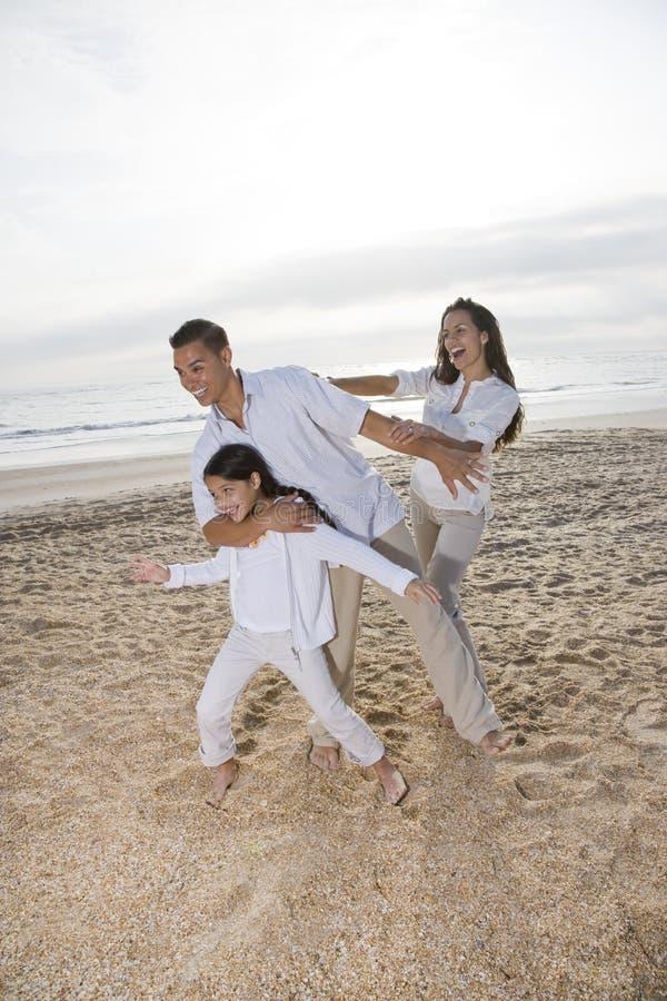 Hispanische Familie mit dem Mädchen, das Spaß auf Strand hat stockfotos