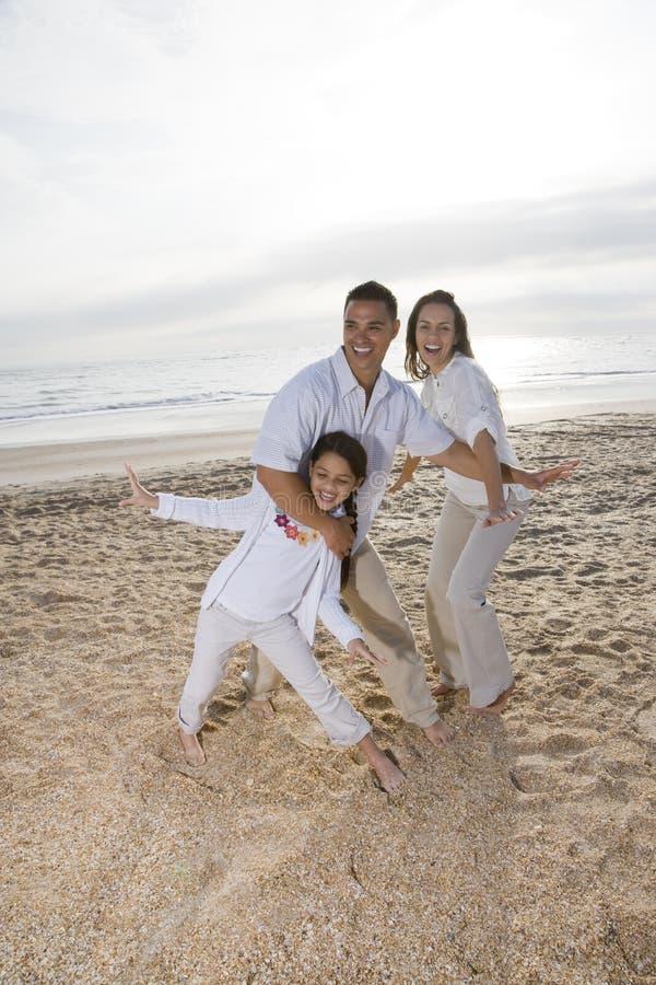 Hispanische Familie mit dem Mädchen, das Spaß auf Strand hat lizenzfreie stockbilder