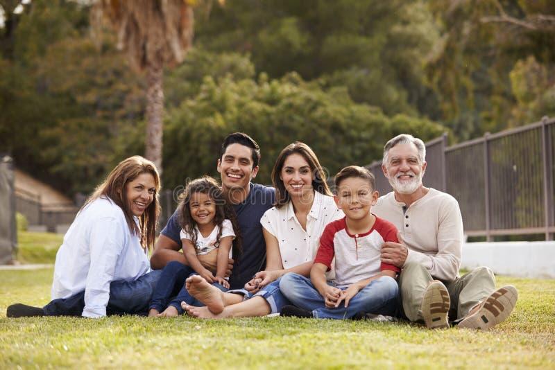 Hispanische Familie mit drei Generationen, die auf dem Gras im Park lächelnd zur Kamera, selektiver Fokus sitzt stockfotos