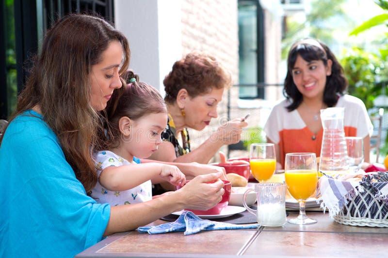 Hispanische Familie mit einem Mädchenkleinkind, das zusammen frühstückt lizenzfreies stockbild