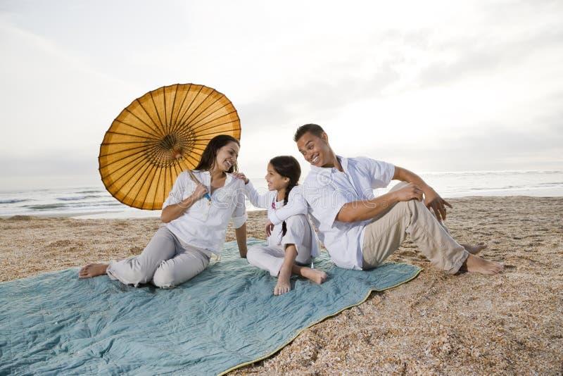 Hispanische Familie mit kleinem Mädchen auf Stranddecke lizenzfreies stockbild