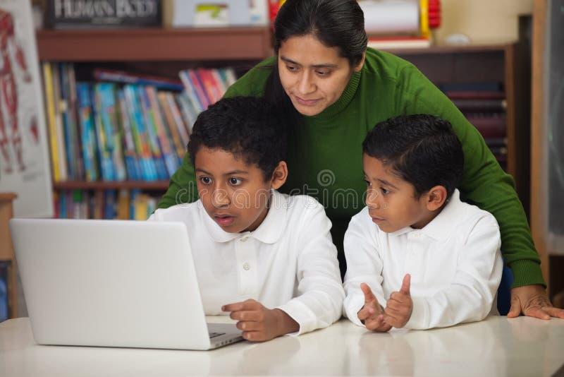 Hispanische Familie mit Laptop in der Schulumgebung stockfotografie