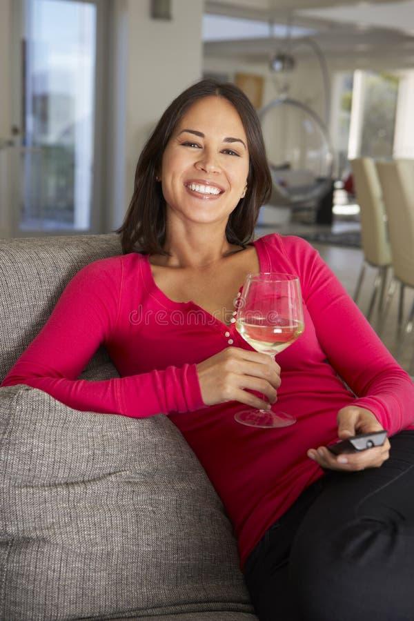 Hispanische Frau auf Sofa Watching Fernsehtrinkendem Wein stockbild