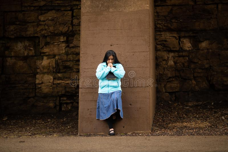 Hispanische Frau betet durch Wand lizenzfreies stockfoto