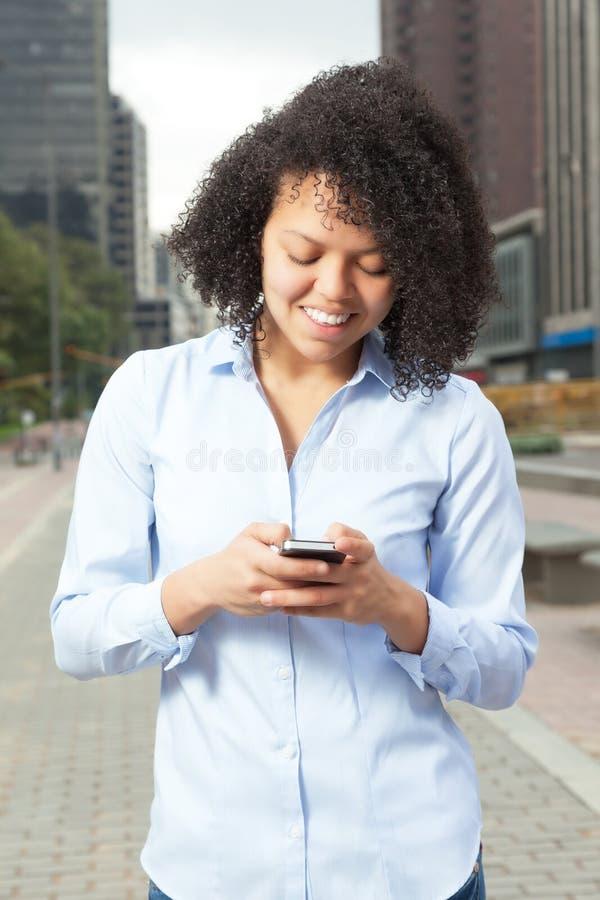 Hispanische Frau in der Stadtschreibensmitteilung mit Telefon lizenzfreie stockfotos