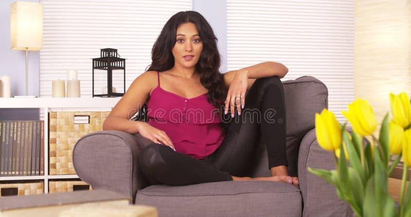 Hispanische Frau, die auf Couch sitzt lizenzfreies stockbild