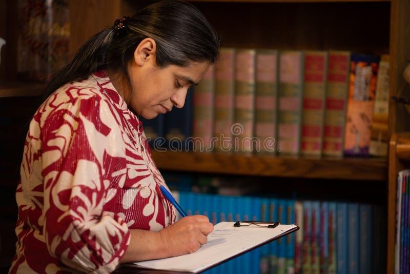 Hispanische Frau, die auf Papier schreibt lizenzfreie stockfotos