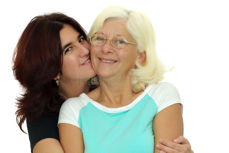 Hispanische Frau, die ihre Mutter getrennt auf Whit umarmt stockbild