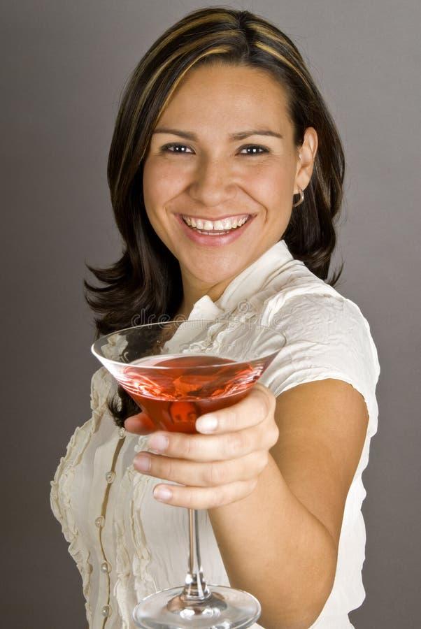 Hispanische Frau, die mit einem Martini röstet lizenzfreie stockfotografie