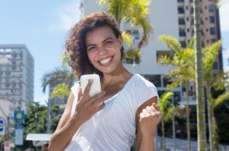 Hispanische Frau, die telefonisch gute Nachrichten empfängt lizenzfreies stockbild
