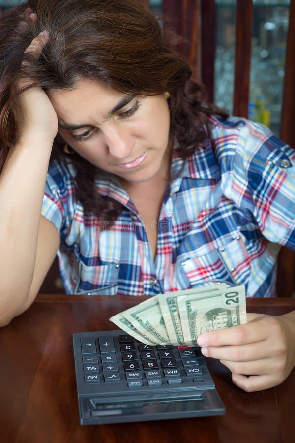 Hispanische Frau, die zu Hause Geld zählt, um die Wechsel einzulösen lizenzfreies stockbild