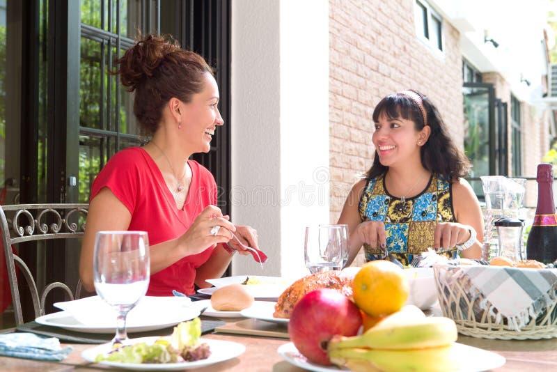 Hispanische Frauen, die zusammen eine Hauptmahlzeit im Freien genießen stockfotografie