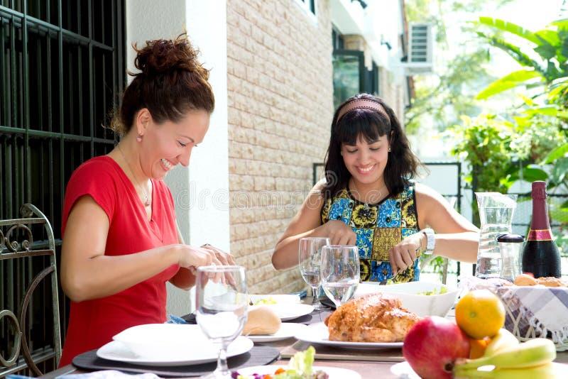 Hispanische Frauen, die zusammen eine Hauptmahlzeit im Freien genießen stockbilder