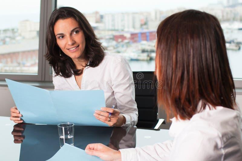 Hispanische Geschäftsfrau, die eine positive Bewertung von einem Angestellten macht lizenzfreies stockfoto