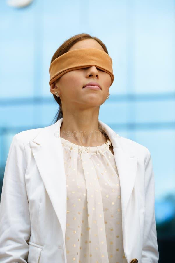 Hispanische Geschäftsfrau mit verbundenen Augen nahe Bürogebäude stockbild