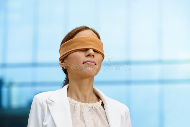 Hispanische Geschäftsfrau mit verbundenen Augen nahe Bürogebäude lizenzfreies stockfoto