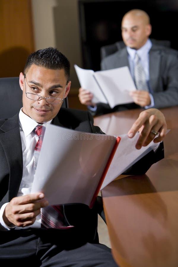 Hispanische Geschäftsmänner im Sitzungssaalüberprüfungreport lizenzfreies stockbild