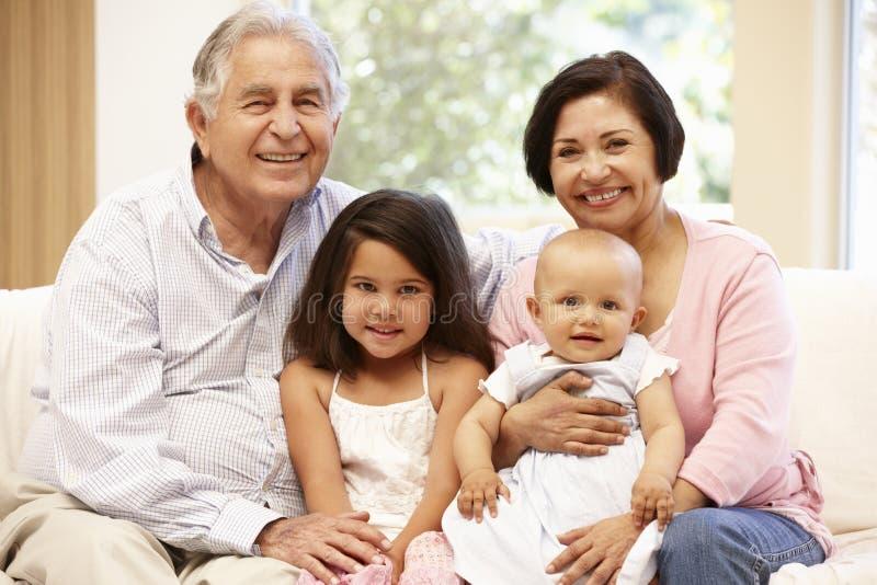 Hispanische Großeltern zu Hause mit Enkelkindern lizenzfreie stockbilder