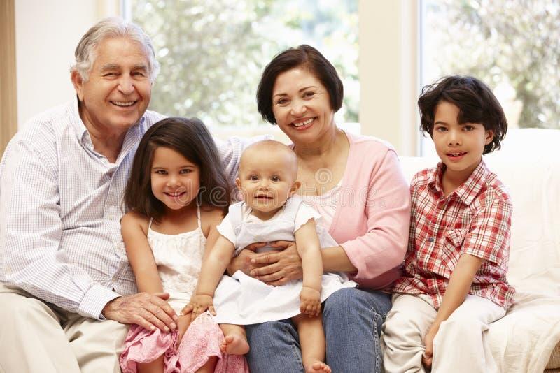 Hispanische Großeltern zu Hause mit Enkelkindern lizenzfreies stockbild