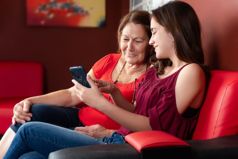 Hispanische Jugendliche und ihre Großmutter, die einen Smartphone und ein Lächeln betrachtet lizenzfreie stockfotos