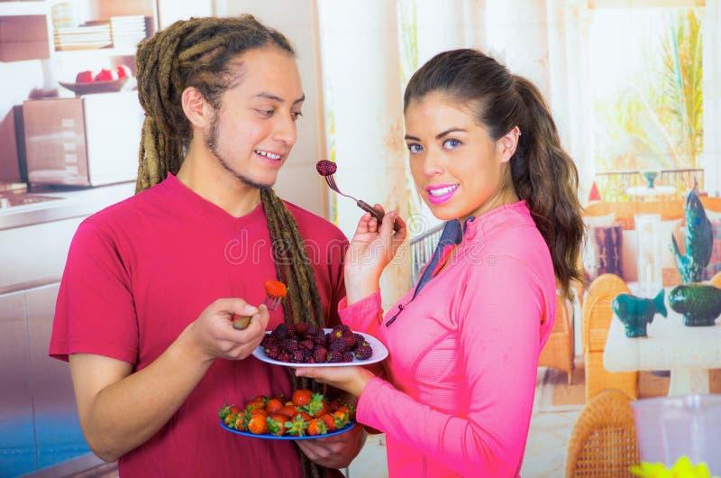 Hispanische junge gesunde Frühstück zusammen genießende, Brombeeren teilende und lächelnde Paare, Hauptküchenhintergrund lizenzfreies stockbild