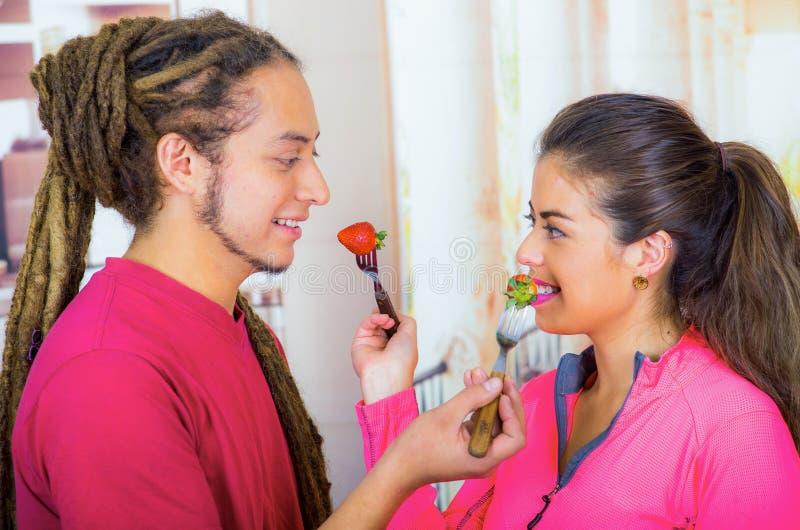 Hispanische junge gesunde Frühstück zusammen genießende, Erdbeeren teilende und lächelnde Paare, Hauptküchenhintergrund lizenzfreies stockfoto