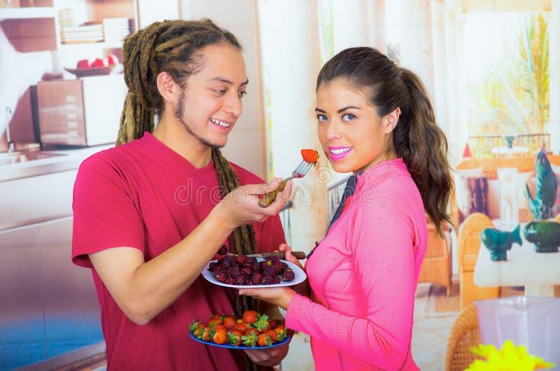 Hispanische junge gesunde Frühstück zusammen genießende, Früchte teilende und lächelnde Paare, Hauptküchenhintergrund stockbilder