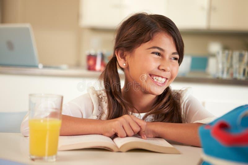 Hispanische Mädchen-Lesehausarbeit bei Tisch lizenzfreie stockfotos