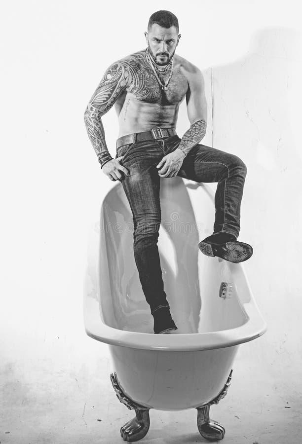 Hispanische man met spierromp op badrand Brutal latino man ontspannend in bad Spa-bad en jacuzzi Zwart stock foto's