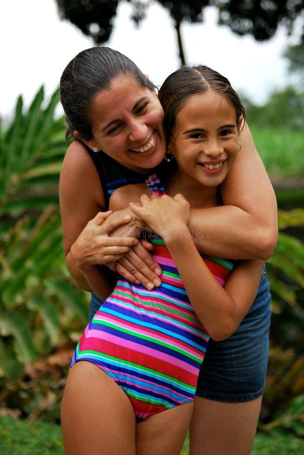 Hispanische Mutter, die ihre Tochter umarmt stockfoto
