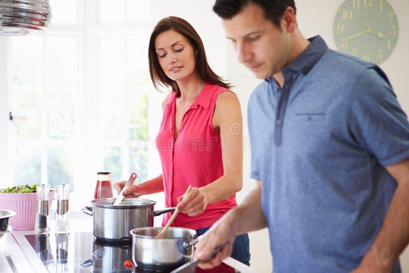 Hispanische Paare, die zu Hause Mahlzeit kochen lizenzfreie stockbilder