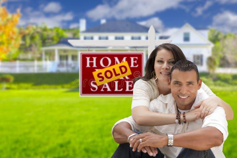 Hispanische Paare, neues Haus und Verkaufs-Real Estate-Zeichen lizenzfreies stockfoto