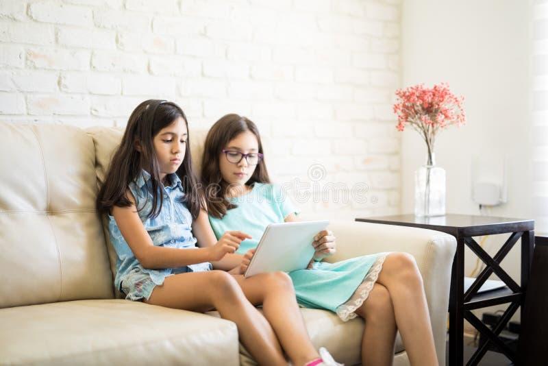 Hispanische Schwestern, die Tablette auf dem Sofa im Wohnzimmer verwenden stockfotos