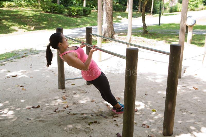 Hispanische Sportfrau, die Laufleinen mit rosa Dummkopf tut lizenzfreies stockbild