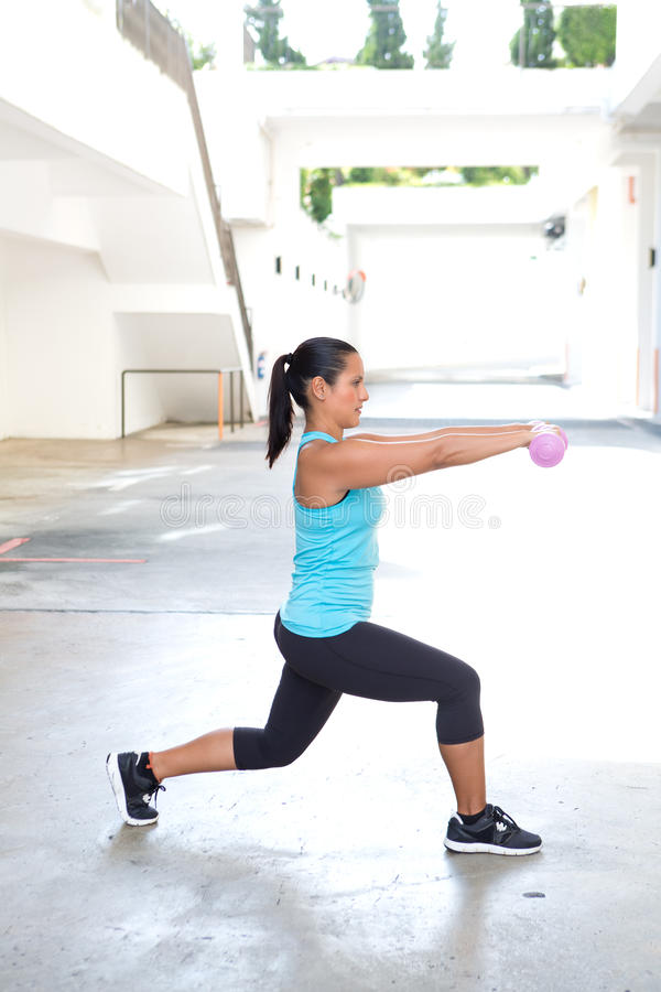 Hispanische Sportfrau, die Laufleinen mit rosa Dummkopf tut stockbild