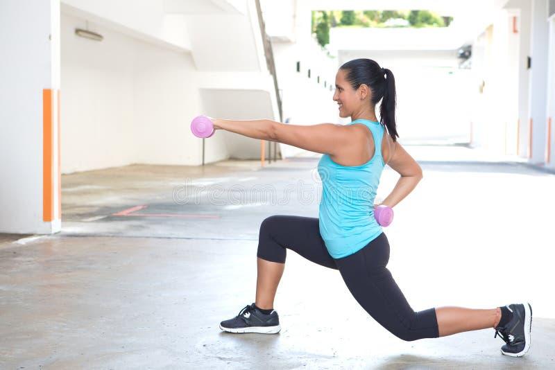 Hispanische Sportfrau, die Laufleinen mit rosa Dummkopf tut lizenzfreie stockfotografie