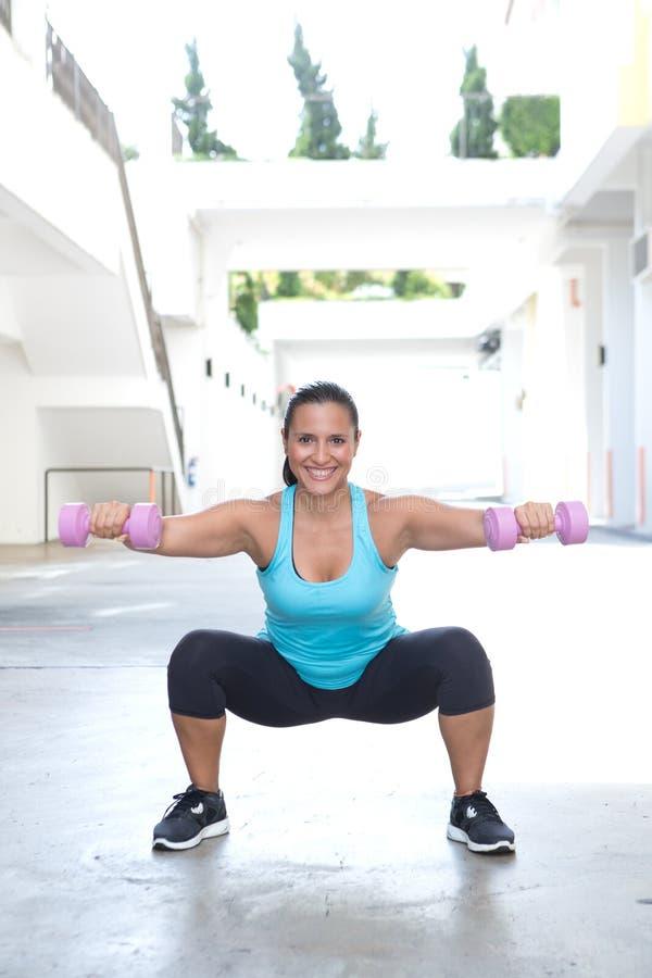 Hispanische Sportfrau, die Laufleinen mit rosa Dummkopf tut lizenzfreie stockfotos