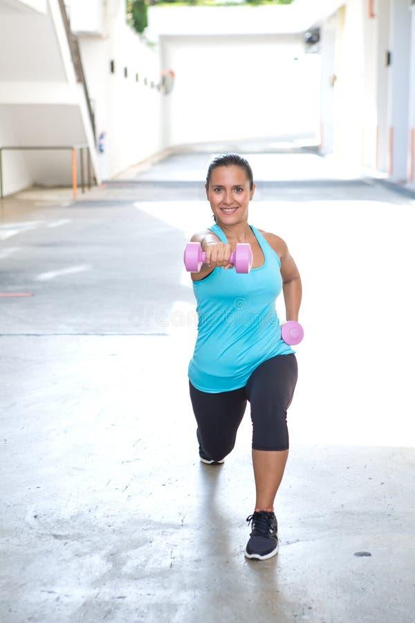 Hispanische Sportfrau, die Laufleinen mit rosa Dummkopf tut stockfotografie